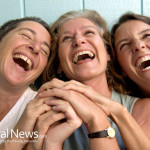 Woman-Friends-Laughing-Hold-Hands