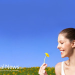 Woman-Smiling-Smelling-Flower-Daisy-Field